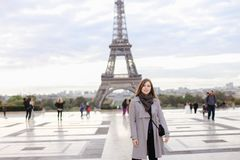 Young woman in grey coat standing near Eiffel Tower in Paris. stock image