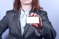 Young woman  in grey suit holds business card Stock Photos