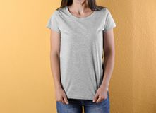 Young woman in grey t-shirt on color background royalty free stock image