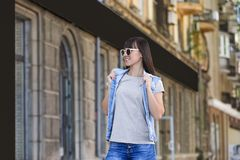 Young woman in grey t-shirt and denim vest outdoors. Mockup for design royalty free stock images