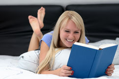 Young woman grinning as she reads a book royalty free stock photo