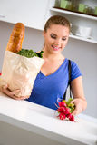 Young woman with groceries in shopping bag Royalty Free Stock Photography