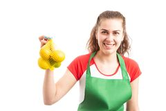 Young woman grocery or retail worker holding lemon bag. As fresh vitamin natural product promotion concept isolated on white background royalty free stock photography