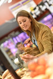 Young woman at grocery store buying fruits Royalty Free Stock Photo