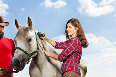 Young woman grooming the mane of her white horse Stock Photo