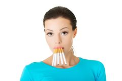 Young woman with group of cigarettes in mouth Royalty Free Stock Photos
