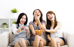 Young woman group  eating snacks and watching the tv. Happy young women group  eating snacks and watching the tv Royalty Free Stock Images