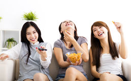 Young woman group  eating snacks and watching the tv Stock Photography