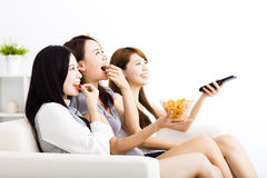 Young woman group  eating snacks and watching the tv. Happy young women group  eating snacks and watching the tv Royalty Free Stock Image