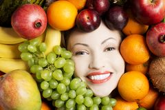 Young woman in group of fruit. Royalty Free Stock Images