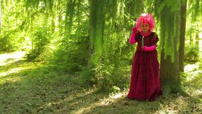 A young woman in the guise of a witch in a forest with a candle is engaged in magic. Overall plan stock footage