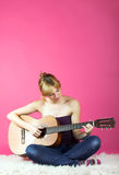 Young woman with a guitar. A young beautiful woman is playing a guitar on a carpet Stock Image