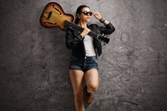Young woman with guitar on her shoulder leaning on rusty gray wa Stock Images