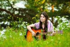 Young woman with guitar outdoors. In summer Royalty Free Stock Photography
