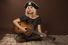 Young woman with guitar. In pirate hat Royalty Free Stock Image