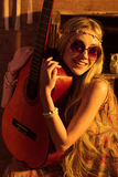 Young woman with guitar. Young smiling woman hippie in sunglasses holding guitar Royalty Free Stock Photo