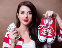 Young woman with gumshoes and money. Portrait of beautiful young woman with red gumshoes and money on the brown background Royalty Free Stock Photo