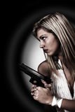 Young woman with gun. On black Stock Photo
