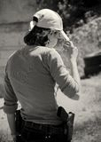 Young woman with gun. Photographed from the back Stock Photo
