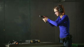 Young woman with the gun on an indoor shooting range. collect gun stock video footage