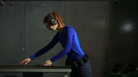Young woman with the gun on an indoor shooting range. preparation for shooting stock video