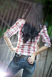 Young woman with guns backside view. Shallow dof and light flash effect Royalty Free Stock Photo
