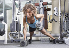 Young woman in the gym. Woman working out with weights in a gym Stock Image