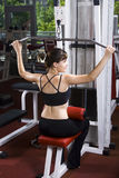 Young woman in the gym. Young woman is doing exercises in a fitness room / gym Stock Photography