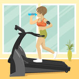 Young woman at gym doing exercise on treadmill with smartphone armband drinking water Royalty Free Stock Image