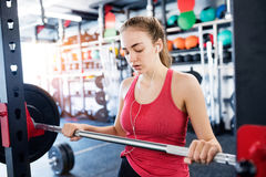 Young woman in gym, earphones in her ears,listening music Stock Photo