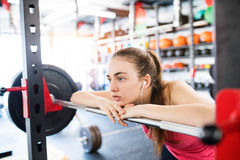 Young woman in gym, earphones in her ears,listening music Royalty Free Stock Photo
