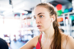 Young woman in gym, earphones in her ears,listening music Royalty Free Stock Image
