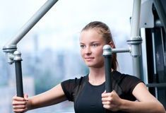 Young woman at the gym exercising Stock Images