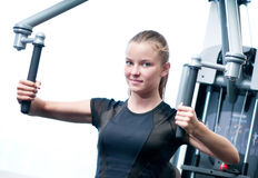 Young woman at the gym exercising Stock Photography