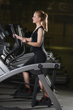 Young woman at the gym exercising. Run on machine. Royalty Free Stock Photo