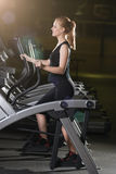 Young woman at the gym exercising. Run on machine. Royalty Free Stock Image