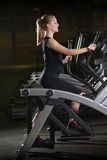 Young woman at the gym exercising. Run on machine. Stock Images
