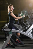 Young woman at the gym exercising. Run on machine. Stock Image