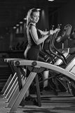 Young woman at the gym exercising. Run on machine. Stock Photography