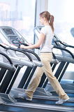 Young woman at the gym exercising. Running Stock Image