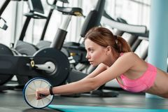 Young girl in gym healthy lifestyle lying on mat rolling ab wheel side view royalty free stock images