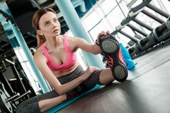 Young girl in gym healthy lifestyle sitting on mat stretching leg looking forward curious close-up stock photography