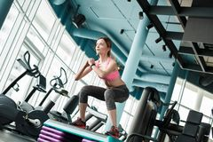Young girl in gym healthy lifestyle squatting on stepper exhale stock photography
