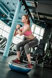 Young girl in gym healthy lifestyle standing on bosu trainer squatting royalty free stock image