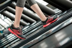 Young girl in gym healthy lifestyle walking on treadmill sneakers close-up stock images