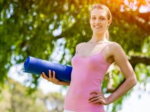 Young woman with a gym mat in the park Royalty Free Stock Photography