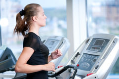 Young woman at the gym. Run on a machine Royalty Free Stock Images