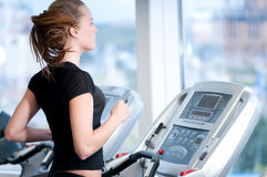 Young woman at the gym. Run on a machine Stock Photography
