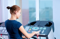 Young woman at the gym run on on a machine Stock Image