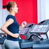 Young woman at the gym run on on a machine Stock Photos